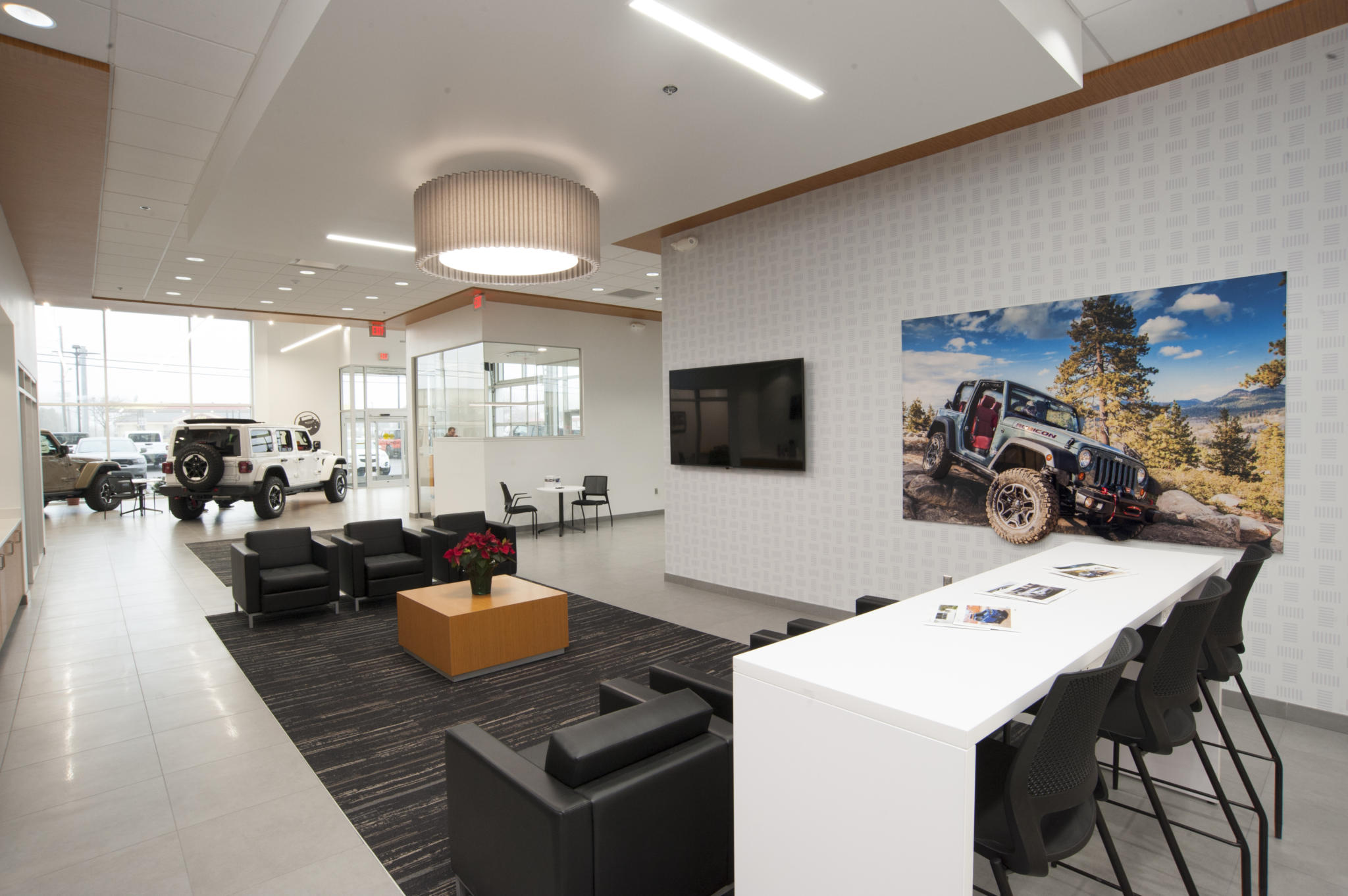 image of waiting room at car dealership, tv on wall, chairs to sit on